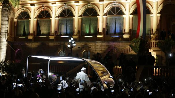 Pope Francis stands in his popemobile as he is driven away from the Lopez Presidential Palace, in Asuncion, Paraguay (AP)