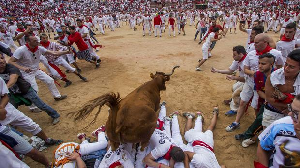 A cow jumps over a group of revelers on the bull ring, at the San Fermin Festival, in Pamplona, Spain (AP)