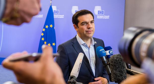 Greek prime minister Alexis Tsipras faces the media after a meeting of eurozone heads of state at the EU Council building in Brussels (AP)
