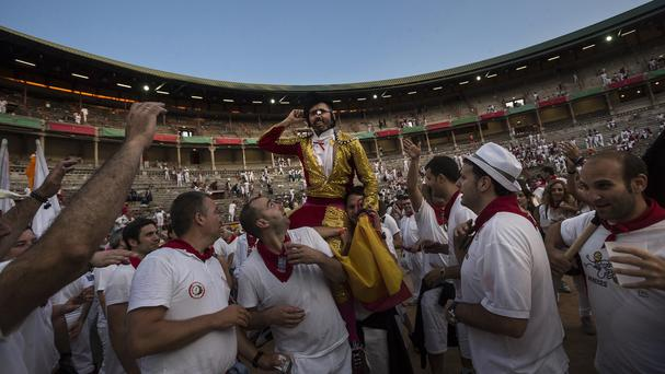 Revellers party in the arena after a bullfight at the San Fermin festival in Pamplona, Spain (AP)