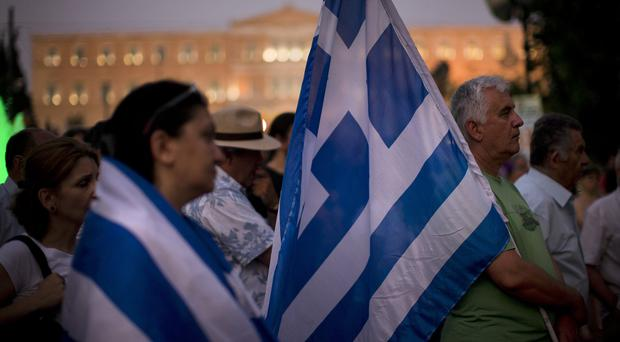 Demonstrators gather near the Greek parliament in Athens during a rally against the government's agreement with its creditors (AP)