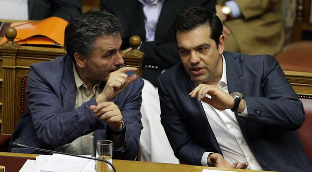Greece's Prime Minister Alexis Tsipras, right, speaks with Finance Minister Euclid Tsakalotos during a parliament meeting in Athens (AP)