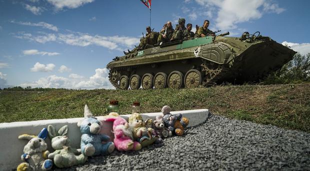 Russia-backed separatists pass a memorial to victims of the plane crash at the crash site near the village of Hrabove (AP)
