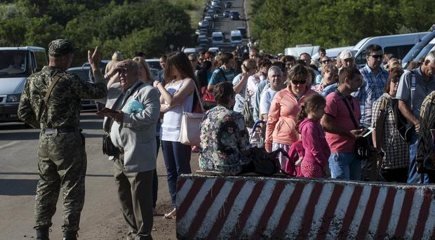 Residents of the Donetsk and Luhansk regions wait to cross a Ukrainian government checkpoint. (AP)