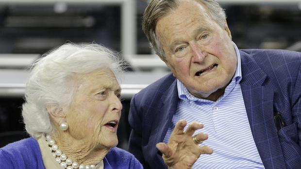 Former US president George HW Bush, pictured earlier this year with his wife Barbara, remains in hospital after fracturing a bone in his neck (AP)