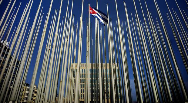 A Cuban flag flies among empty flag poles near the US Interests Section building, behind, in Havana (AP)