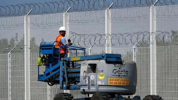 Workers install security fencing along the route into the ferry port in Calais, France (AP)