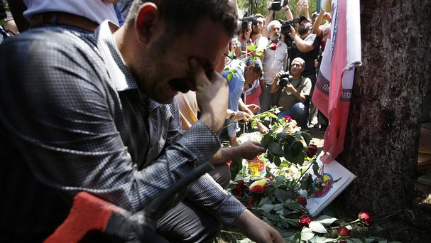 A man lays flowers at the site of a suicide bombing in Suruc, Turkey (AP)