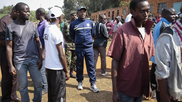 President Pierre Nkurunziza, centre, waits in a queue to cast his vote for the presidential election, in Ngozi, Burundi (AP)