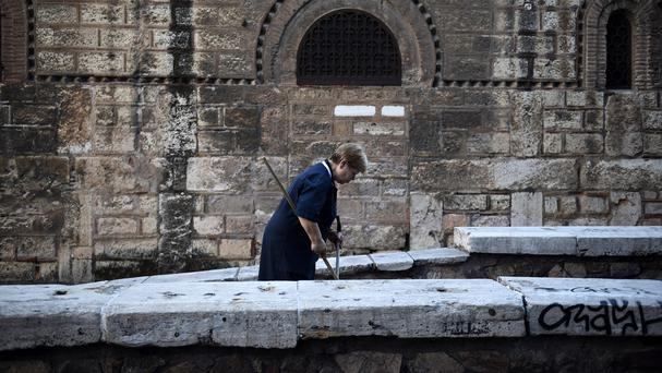 A worker cleans the pavement outside a Greek Orthodox church in Athens (AP)
