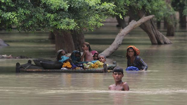 Villagers wade through flood waters in Rajanpur, Pakistan