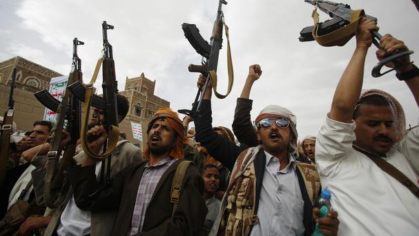 Shiite rebels known as Houthis hold up their weapons as they chant slogans during a rally against Saudi-led airstrikes in Sanaa (AP)