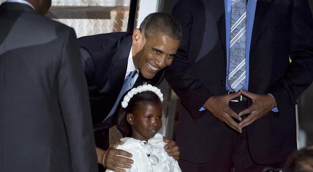 Obama poses for a photograph with Joan Wamaitha, 8, who gave him flowers on his arrival in Kenya (AP)