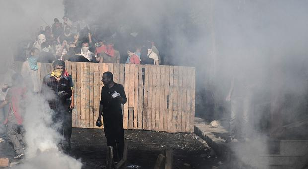 Protesters man a barricade as tear gas fired by police fills the street in Istanbul during clashes with police after the deaths of 32 people at an suicide bombing on Monday (AP)