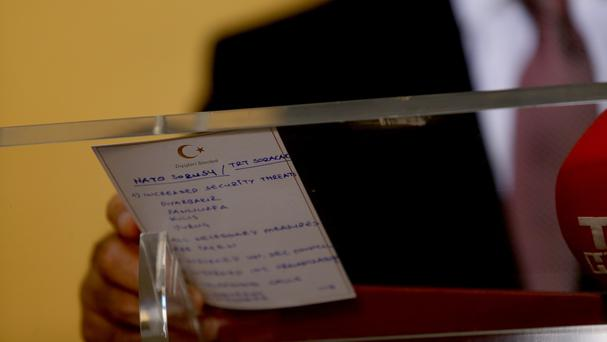 Turkish foreign minister Mevlut Cavusoglu holds a card with his notes about Nato during a news conference on Monday (AP)