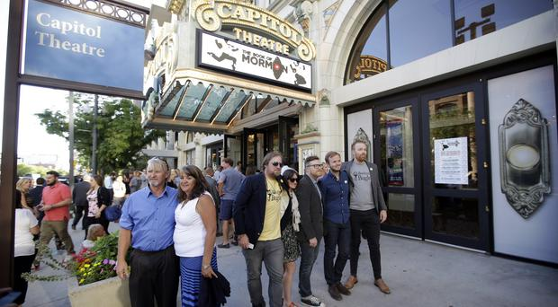 People pose for photographs before entering the Capitol Theatre to see The Book of Mormon musical in Salt Lake City (AP)
