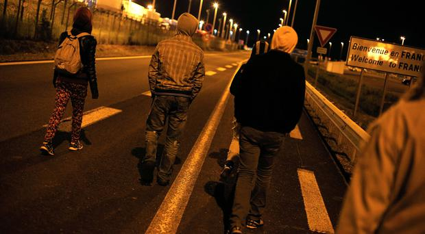 Migrants walk on a road outside the Eurotunnel area in Calais (AP)