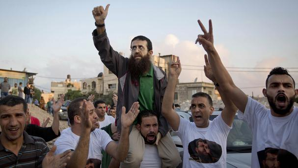 Palestinian Khader Adnan, centre, who recently ended a 55-day hunger strike, is greeted by Palestinians after his release from an Israeli prison (AP)