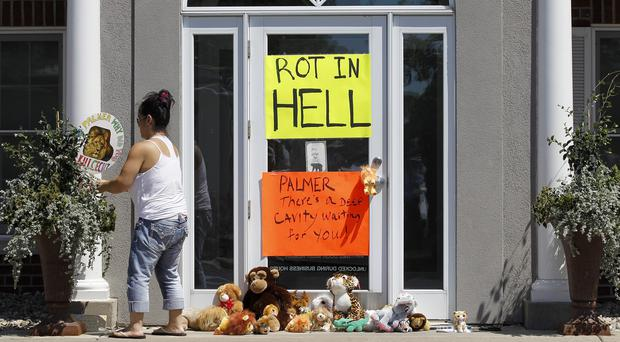 A woman moves a sign outside Dr Walter James Palmer's dental office in Bloomington, Minnesota (AP)