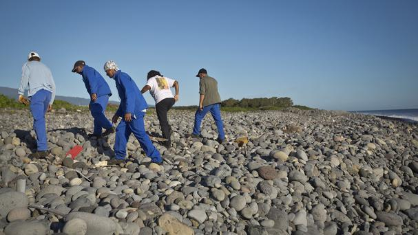 Workers search a beach on Reunion for possible additional debris near the area where an airplane wing part was washed up (AP)