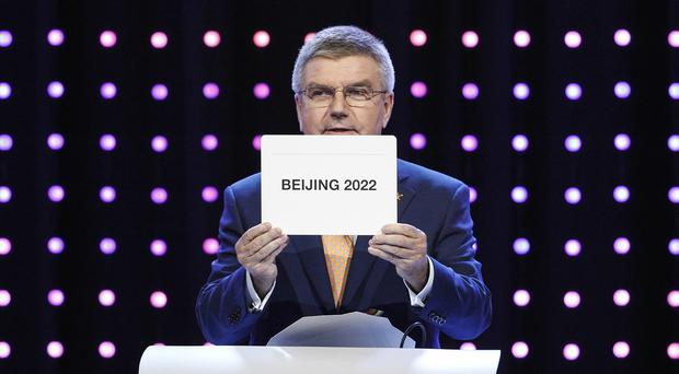 International Olympic Committee president Thomas Bach opens the envelope announcing that Beijing has won the bid to host the 2022 Winter Olympic Games (AP)