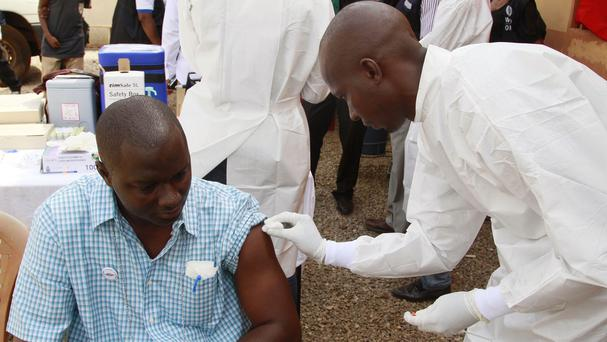 A health worker (right) cleans a man's arm before injecting him with a Ebola vaccine in Conakry, Guinea (AP)