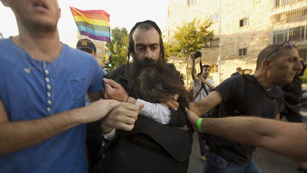 A man is detained by plain-clothes police officers after he stabbed people during a gay pride parade in Jerusalem (AP)