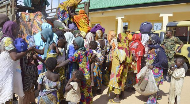 Women and children rescued by Nigerian soldiers from Boko Haram extremists in the north east arrive at the military office in Maiduguri (AP)