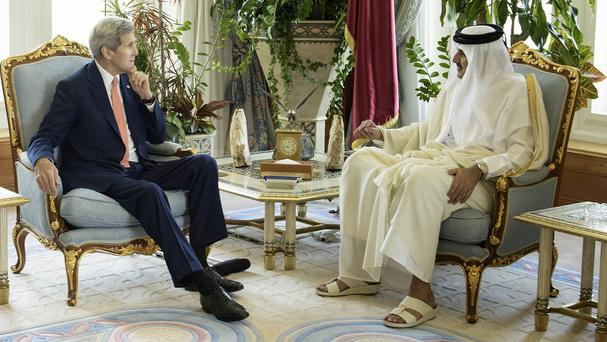 US Secretary of State John Kerry, left, speaks with Qatar Emir Sheik Tamim bin Hamad Al-Thani (AP)