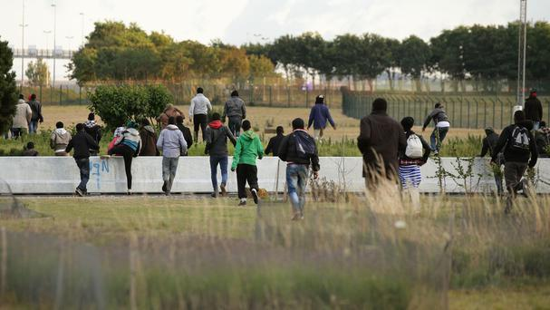 Migrants run towards the perimeter fence of the Eurotunnel site at Coquelles in Calais, France