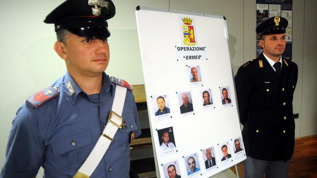 A Carabinieri paramilitary police officer and a police officer stand next to mugshots of 11 men suspected of helping Matteo Messina Denaro (AP)