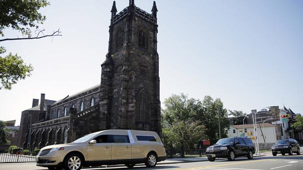 A hearse carrying the coffin bearing the body of Bobby Kristina Brown drives past Saint James Church near Whigham Funeral home in Newark, New Jersey (AP)