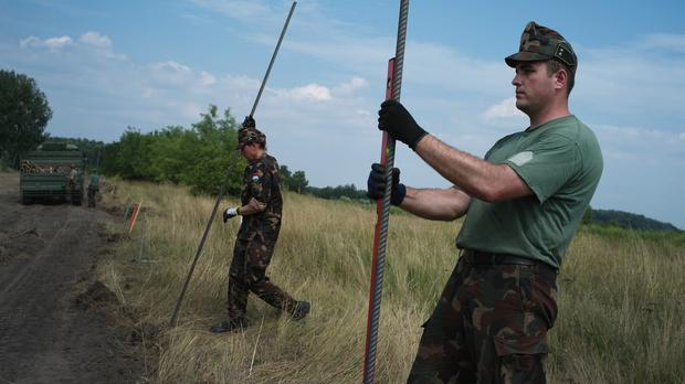 Hungarian soldiers build a fence on the Serbian border near Asotthalom (AP)