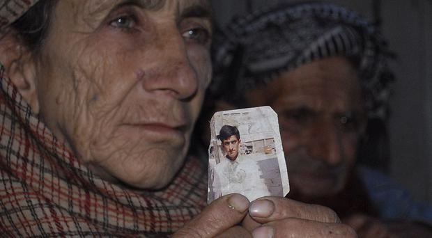 Makhni Begum holds a photograph of her son Shafqat Hussain in Muzaffarabad, Pakistan (AP)