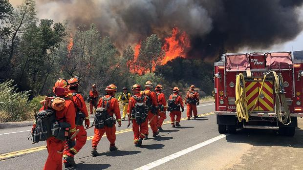 Fire crews walk on US Highway 20 as a fire approaches near Clearlake, California (AP)
