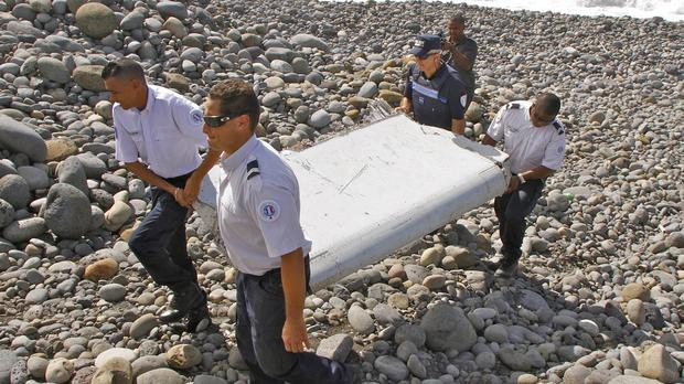 French police officers carry a piece of debris from a plane found in Saint-Andre, Reunion Island (AP)