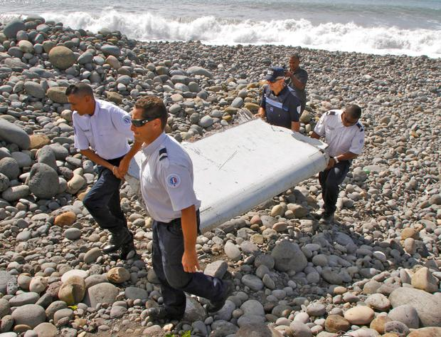 French police officers carrying the plane debris discovered on Reunion Island