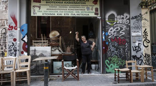 Business owner Katherina Athanasopoulou poses at the entrance of her workshop in central Athens (AP)