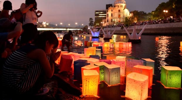 Paper lanterns float on the Motoyasu River in front of the Atomic Bomb Dome in Hiroshima