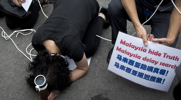 Relatives of the Malaysia Airlines Flight 370 passengers kneel down in front of the media ahead of a briefing given by the airlines outside a help centre in Beijing. (AP)