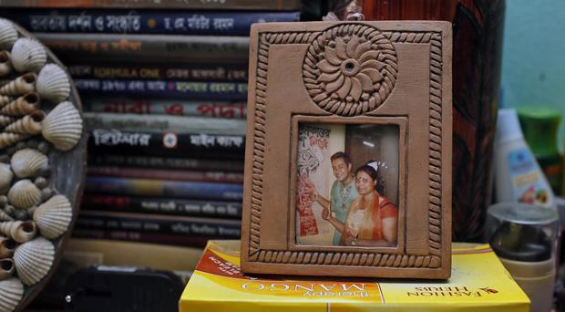 A photo frame displaying portraits of blogger Niloy Chowdhury and his Asha Moni in their room in Dhaka (AP)