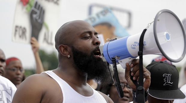 Michael Brown Sr speaks through a megaphone as he takes part in a parade in honour of his son in Ferguson (AP)