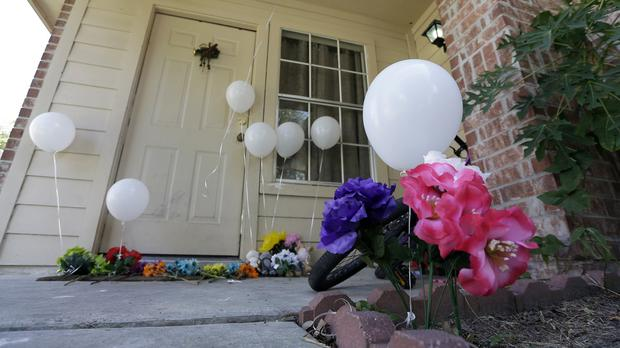 Flowers and eight balloons left at a house where eight people were killed (AP)