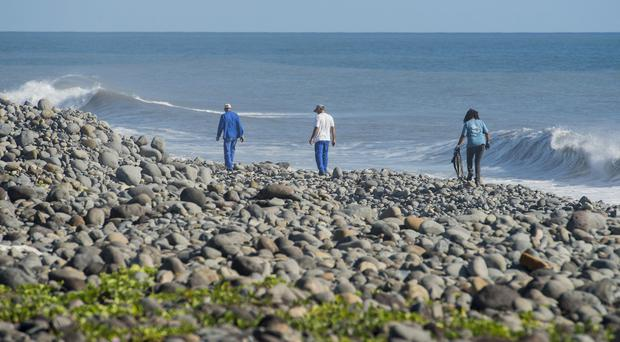 Workers search Reunion Island beaches where debris of the missing Malaysia Airlines Flight 370 could be washed up (AP)