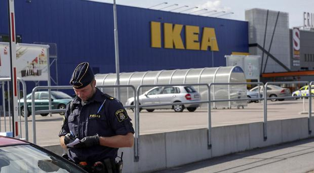 A police office talks to customers outside the Ikea store in Vasteras, Sweden, after a knife attack (Peter Kruger/TT/AP)