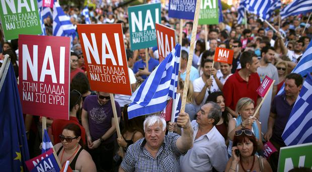 Demonstrators hold Greek flags and placards reading Yes to Greece, Yes to Euro during a rally organised by supporters of the Yes vote in Athens (AP)