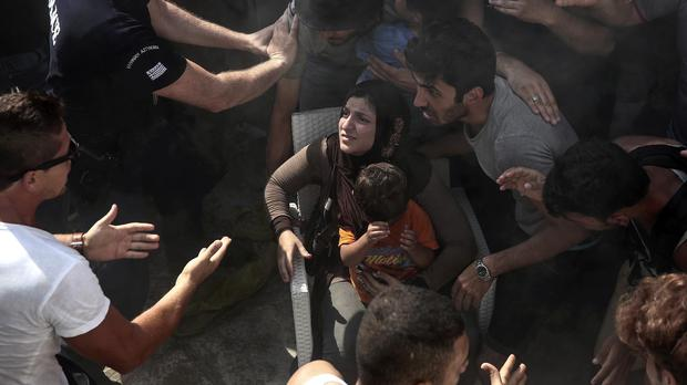 A woman holds a child as police try to hold back migrants on the Greek island of Kos. (AP)