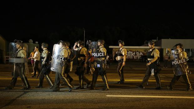Police walk around protesters as people gather along West Florissant Avenue in Ferguson, Missouri (AP)