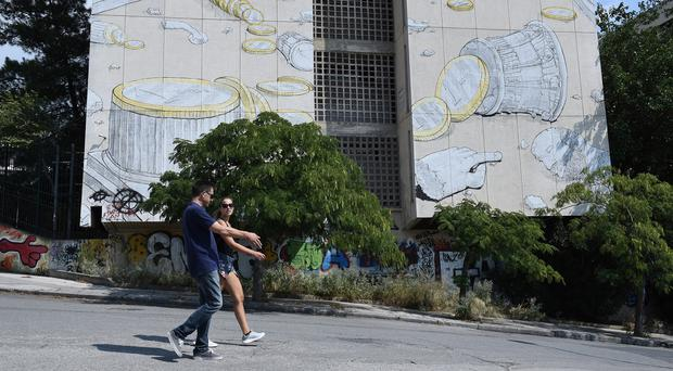 A man and a woman walk in front of graffiti showing Greek euro coins in the northern port city of Thessaloniki (AP)