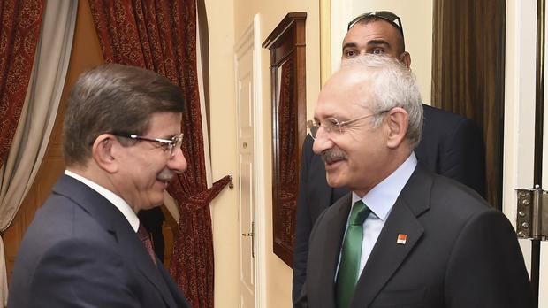 Turkish prime mnister Ahmet Davutoglu, left, shakes hands with the main opposition leader Kemal Kilicdaroglu prior to talks in Ankara (AP)